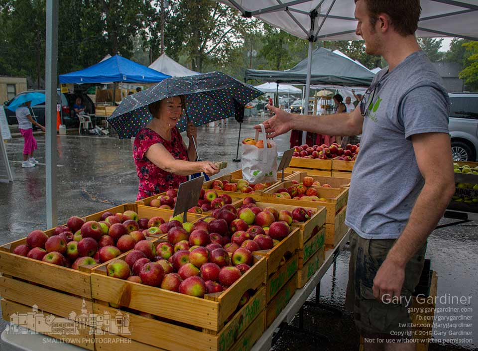 Despite a heavy rain squall, a few shoppers braved the elements to buy apples, vegetables, fruits, breads, and condiments at the Uptown Westerville Farmers Market.